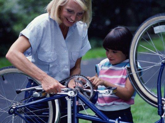 bilde; voksen dame og barn reparer sykkel